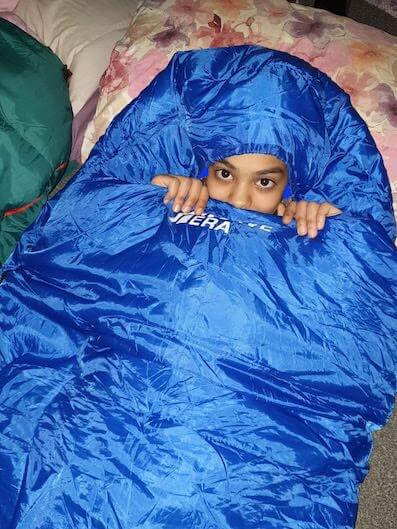 Camping in the garden - child in sleeping bag